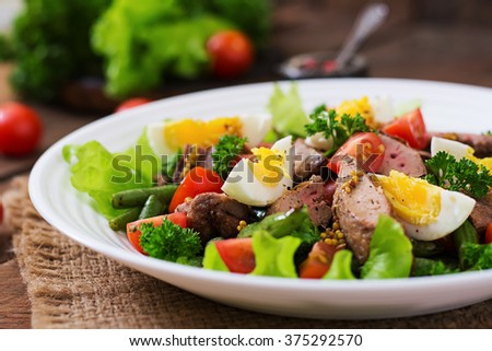Warm salad with chicken liver, green beans, eggs, tomatoes and balsamic dressing - stock photo