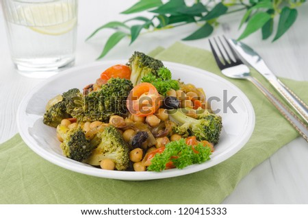 warm salad with chickpeas, broccoli and raisins on the plate, horizontal