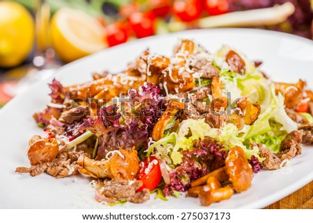 Warm salad with mushrooms, meat and vegetables