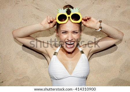 Warm sand treatment. Portrait of cheerful woman in swimsuit with funny pineapple glasses laying on the sand
