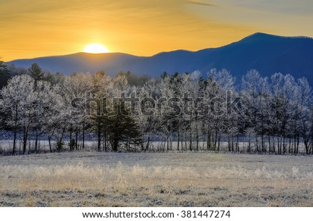 Warm sun rising over a frost covered landscape in Cades Cove of the Great Smoky Mountains - stock photo