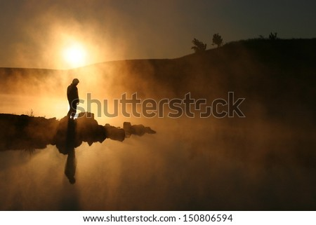 Warm sunrise silhouettes a hiker against a cold early morning mist across a lake.  - stock photo