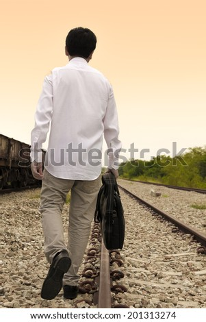 Warm tone color image of Businessman walking on railway