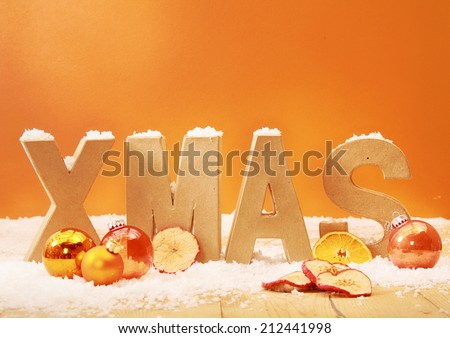 Warm toned Xmas background with wooden letters for Xmas in snow with orange and gold decorations and dried apple and orange slices against an orange background with copyspace - stock photo
