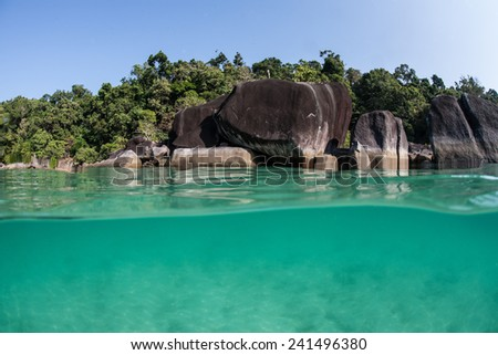 Warm, tropical water bathes the rocky shore of a remote island in the Mergui Archipelago off the coast of Myanmar. These beautiful islands in the Andaman Sea are rarely visited. - stock photo