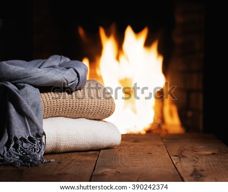 Warm woolen things near fireplace on wooden table. Winter and Christmas holiday concept. - stock photo