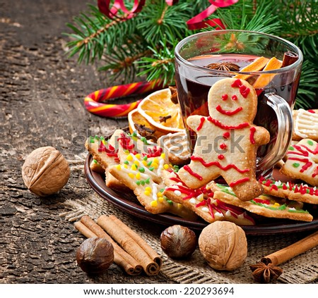 Warming mulled wine, spices and gingerbread cookie on a wooden background in rustic style - stock photo