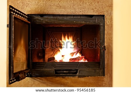 Warming opened fireplace in winter, at home. Close up of flames and firewood
