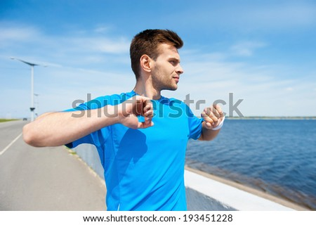 Warming up before jogging. Handsome young man exercising while standing outdoors  - stock photo