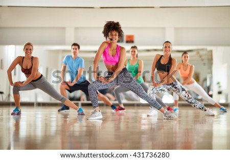 Warming up exercises with female instructor in course at gym - stock photo