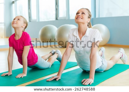 Warming up in sports club. Cheerful mother and daughter doing stretching exercises while lying on exercise mats in sports club  - stock photo