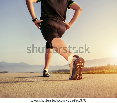 Warming up runner on the road close up image - stock photo