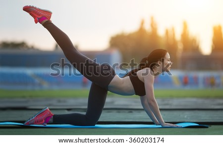 warming-up.young beauty girl do exercises at the stadium