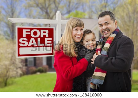 Warmly Dressed Young Mixed Race Family in Front of Home For Sale Real Estate Sign and House. - stock photo