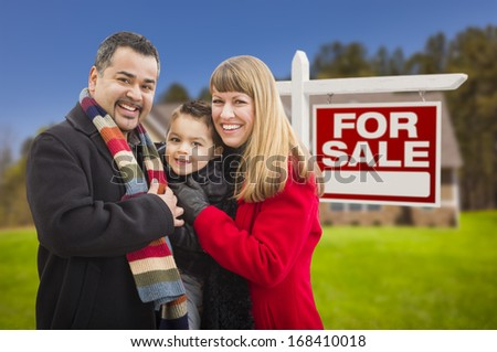 Warmly Dressed Young Mixed Race Family in Front of Home For Sale Real Estate Sign and House.