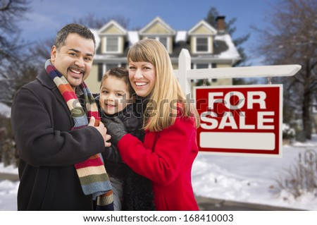 Warmly Dressed Young Mixed Race Family in Front of Home For Sale Real Estate Sign and House with Snow On The Ground.