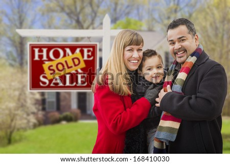 Warmly Dressed Young Mixed Race Family in Front of Sold Home For Sale Real Estate Sign and House. - stock photo