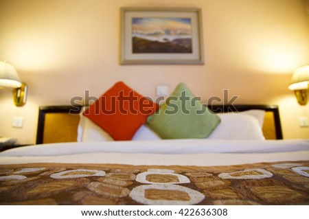 Warmly lit hotel room and bed with shallow depth of field - stock photo