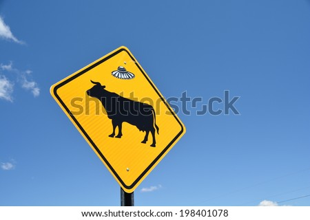 Warning cow sign on blue sky with ufo sticker  - stock photo