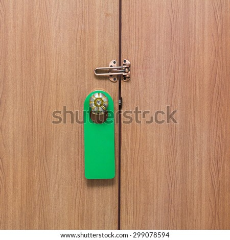 Warning Do Not Disturb sign hanging on the door knob green. - stock photo
