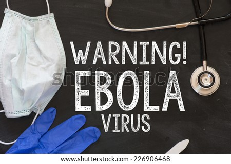 Warning! Ebola virus chalk handwriting. Ebola virus chalk handwriting on blackboard. Stethoscope, glove, mask on blackboard. - stock photo