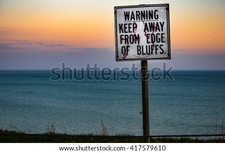 Warning Keep Away From Edge of Bluffs sign overlooking Lake Ontario at Toronto, Ontario, Canada in the evening.