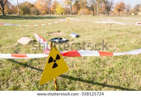 Warning radiation sign marking a hazardous radioactive area in the field. - stock photo