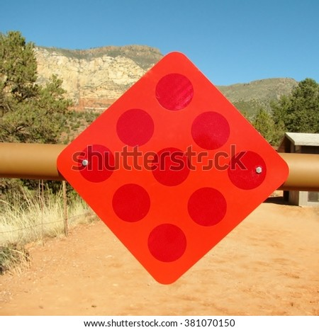 Warning red reflector sign hanging on the blocking way barrier - stock photo