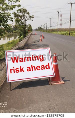 warning risk ahead, Cracked asphalt road - stock photo