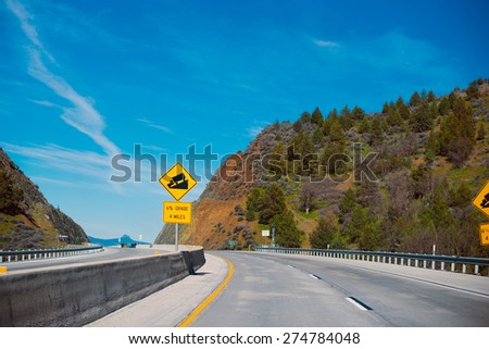 Warning road sign ahead of the upcoming downhill for semi truck mounted on a multi highway with a border separating the hills covered with trees, drifting into the horizon. - stock photo