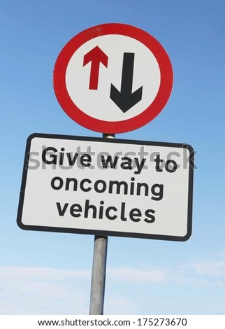 Warning road sign requiring motorists to give way to oncoming traffic. - stock photo