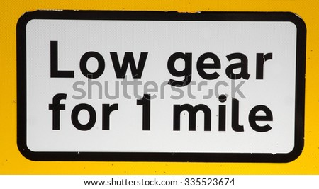 Warning road sign to keep in a Low Gear for one Mile due to a Long Descent down The Snake Pass, Derbyshire, UK. - stock photo