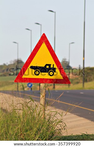 Warning road sign with a construction truck in a red triangle on the side of the road. - stock photo