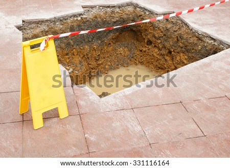 Warning sign and a hole on the road - stock photo