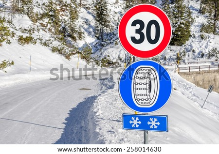 Warning Sign and Speed Limit on a Treacherous Mountain Road in Winter - stock photo