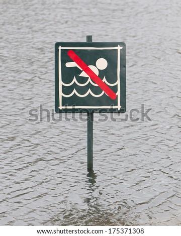 Warning sign at a lake, Caution No Swimming allowed - stock photo