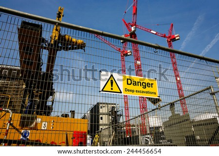 warning sign at construction site, multiple cranes working in the background  - stock photo