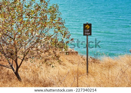 Warning sign cliff edge with a tree - stock photo