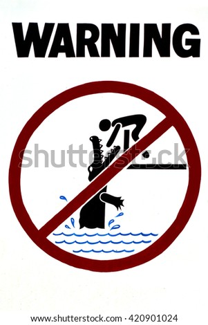 Warning sign - danger crocodile infested waters, no swimming - caution in nature in The tropical north of Queensland, Australia. - stock photo