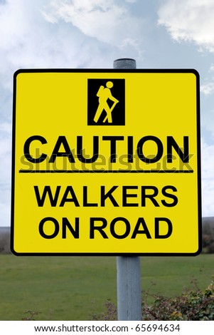 warning sign for drivers to be careful of tourists walking on country roads with clipping path - stock photo
