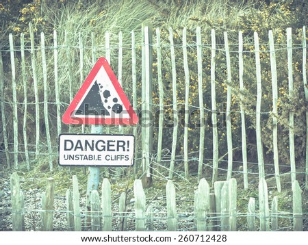 Warning sign for falling rocks from a cliff in the UK with a retro filter applied - stock photo