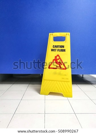 Warning Sign for wet floor cleaning in process in toilet.
