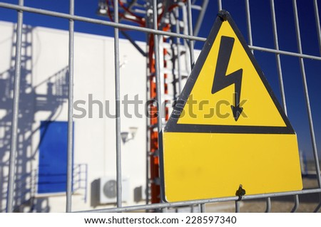 Warning sign high voltage with blue sky - stock photo
