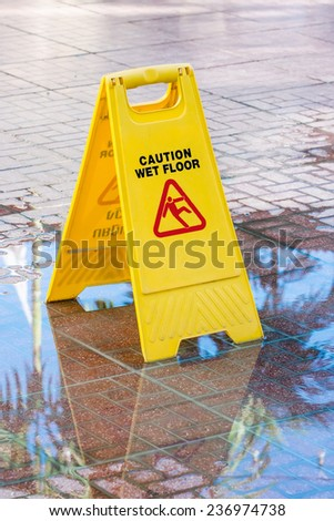 Warning sign in yellow with caution wet floor and the floor is get wet. - stock photo