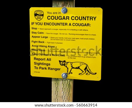 warning sign isolated on black indicating that cougars are in the area posted at Fort Stevens State Park in Oregon