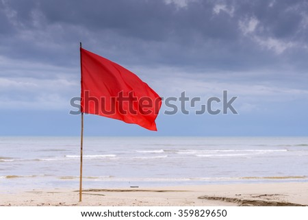 warning sign of a red flag at a beautiful beach with a blue sky and a turquoise sea. - stock photo