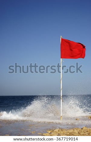 warning sign of a red flag at a beautiful beach with a blue sky and waves making big splashes - stock photo