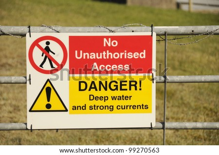 Warning sign on a gate saying no unauthorised access and advising of deep water and strong currents.