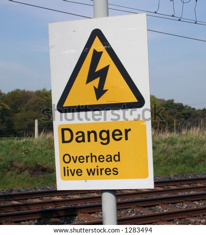 Warning sign on railway lines with wires.
