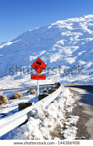 warning sign on the slippery snowy road going to Queenstown New Zealand - stock photo